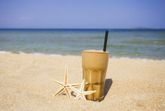 Iced coffee on a sandy beach background stock photo