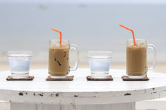 Iced coffee with straw and glass of water Stock Photography