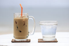 Iced coffee with straw and glass of water Stock Photo