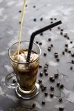 Iced coffee - summer drink. Preparation of cold coffee with milk and ice. Summer cooling drink Stock Photos