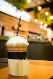 Iced coffee in takeaway cup on wood table with blurred coffee Royalty Free Stock Images