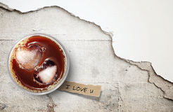 Iced coffee and torn paper on cracked concrete floor. Royalty Free Stock Photos