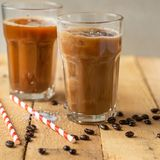 Iced coffee in transparent glasses with ice and straws, on a wooden background, a cooling drink.  stock photos