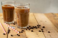 Iced coffee in transparent glasses with ice and straws, on a wooden background, a cooling drink.  stock images