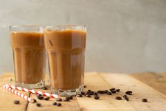 Iced coffee in transparent glasses with ice and straws, on a wooden background, a cooling drink.  royalty free stock photo