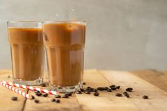 Iced coffee in transparent glasses with ice and straws, on a wooden background, a cooling drink.  stock photo
