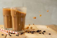 Iced coffee in transparent glasses with ice and straws, on a wooden background, a cooling drink.  royalty free stock image