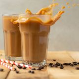 Iced coffee in transparent glasses with ice and straws, on a wooden background, a cooling drink.  royalty free stock images