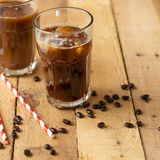 Iced coffee in transparent glasses with ice and straws, on a wooden background, a cooling drink, refreshing, summer mood.  stock photography