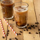Iced coffee in transparent glasses with ice and straws, on a wooden background, a cooling drink, refreshing, summer mood.  stock image