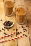 Iced coffee in transparent glasses with ice and straws, on a wooden background, a cooling drink, refreshing, summer mood.  royalty free stock photos