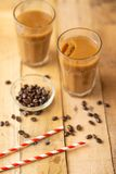 Iced coffee in transparent glasses with ice and straws, on a wooden background, a cooling drink, refreshing, summer mood.  royalty free stock photography