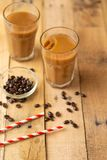Iced coffee in transparent glasses with ice and straws, on a wooden background, a cooling drink, refreshing, summer mood.  stock photo