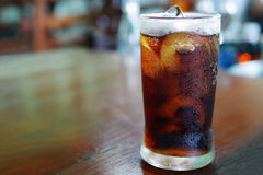 Iced cola with water drops condensed on glass surface, shallow d Royalty Free Stock Photo