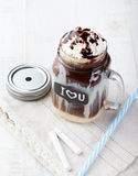 Iced cold coffee, frapuccino with whipped cream and chocolate syrup in jar with chalkboard I Love You on a white table Stock Photos