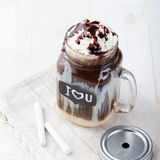 Iced cold coffee, frapuccino with whipped cream and chocolate syrup in jar with chalkboard I Love You on a white table Royalty Free Stock Image