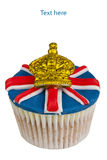 Iced cupcake. Cupcake decorated with Union Jack and golden crown icing isolated on white Royalty Free Stock Image