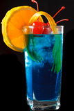 Iced curacao cocktail with orange. Delicious tropical iced blue curacao cocktail garnished with a fresh orange slice and maraschino cherries on a black stock photo