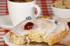 Iced danish pastry. Whirl with cup of coffee and sugar cubes Stock Image