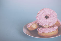 Iced doughnut on a light blue background Vintage Retro Filter. Iced doughnut on a light coloured blue background Vintage Retro Filter stock image