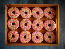 Iced doughnut rings with rainbow sparkl strands. Stock Images