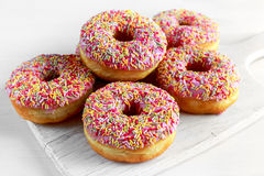 Iced doughnut rings with rainbow sparkl strands. Stock Photos