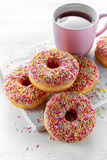 Iced doughnut rings with rainbow sparkl strands and cup of coffee, tea Royalty Free Stock Photos