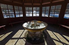 Iced fountain of thermal water inside a gazebo. A partially iced fountain of thermal water inside a wooden gazebo in the village of Bagni di Lusnizza Italy Stock Image