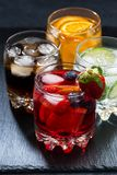 Iced fruit drinks on a dark background, vertical, closeup. Iced fruit drinks on a dark background, closeup royalty free stock image
