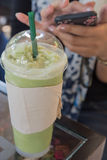 Iced green. Girl Casual Activity Chilling Relaxation Outdoor Concept and Iced green tea latte on the table in coffee shop stock image