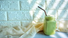 Iced green tea latte. A glass of iced green tea latte royalty free stock image