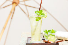 Iced green tea with lime garnish. And ice cube royalty free stock images