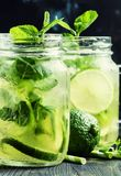Iced green tea with lime and mint in glass jars, dark background. Selective focus stock photography