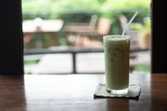 Iced Green tea with a straw. On wood table stock images