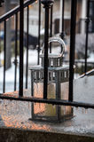 Iced lantern for candle behind metal front porch railings. Photo taken in Toronto, Canada during the ice storm in December of 2013 Stock Image