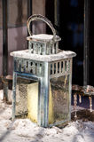 Iced lantern for candle in front of metal front porch railings Royalty Free Stock Photos