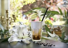 Iced latte coffee glass on table in retro restaurant and café against the background of a window and white lilies. royalty free stock image