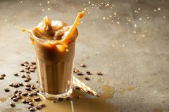 Iced latte coffee splash with ice cubes and roasted beans on a dark background. With copy space royalty free stock images