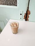 Iced latte in glass with straw, white table, vintage door Stock Photo
