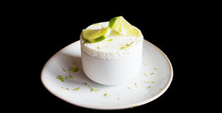Iced lemon souffle. Isolated iced lemon souffle in white cup with pice of lemon on top royalty free stock photos