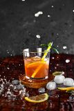 Iced lemon tea in motion concept. Iced lemon tea on dark background in glass and flying in air ingredients. Levitation effect. Summer cold Iced tea. Food in Stock Photography