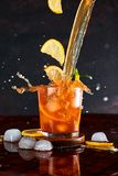 Iced lemon tea in motion concept. Iced lemon tea on dark background in glass and flying in air ingredients. Levitation effect. Summer cold Iced tea. Food in Stock Image