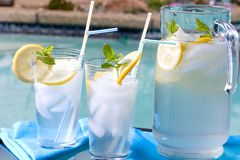 Iced lemonade. Two glasses of home made iced cold lemonade and pitcher on hot summer on edge of swimming pool Stock Images