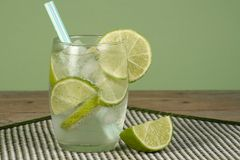 Iced lemonade and lime juice. Glas of lemonade with lime juice and lime slices on a wooden table Stock Photo