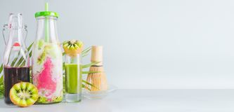 Iced Matcha fusion drink in bottle with ingredients: matcha espresso, red berries juice, kiwi fruits and milk on table with copy. Space. Healthy detox beverage royalty free stock photos