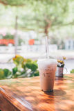 Iced milk coffee in plastic cup on wooden table in tree background Royalty Free Stock Photo