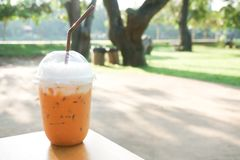 Iced milk tea with plastic takeaway glass on wood table royalty free stock photography