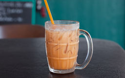 Iced Milk Tea with thai style. On a wooden table Royalty Free Stock Images