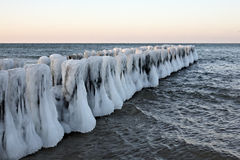 The iced over pier. Winter, frost a minus of ten degrees, coast of Baltic (Kaliningrad), the iced over wooden columns of a breakwater leaving in the sea Royalty Free Stock Photos
