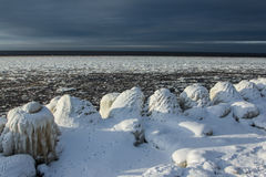 The iced over pier in dark sky. Outside was cold -15degress in Latvia, bolderaja breakwater Royalty Free Stock Image